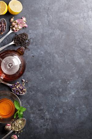 taza de té, la tetera y la variedad de té secas en cucharas en la mesa de piedra. Vista superior con espacio de copia Foto de archivo
