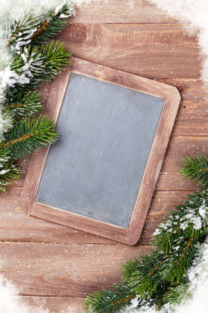 Christmas chalkboard and fir tree with snow on wooden table. Top view with copy space for your text Stock Photo