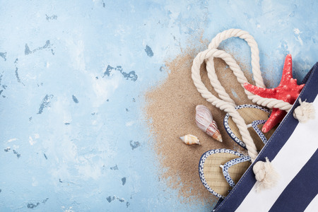 beach view: Beach accessories. Bag, starfish and flip-flops on stone background. Top view with copy space