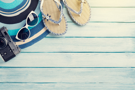 wood board: Beach accessories. Flip flops, camera, hat and sunglasses on wooden background. Top view with copy space. With sun toned