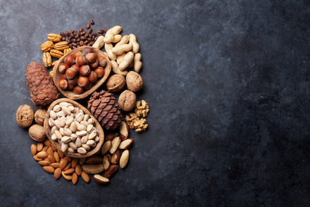 assortment: Various nuts on stone table. Top view with copy space