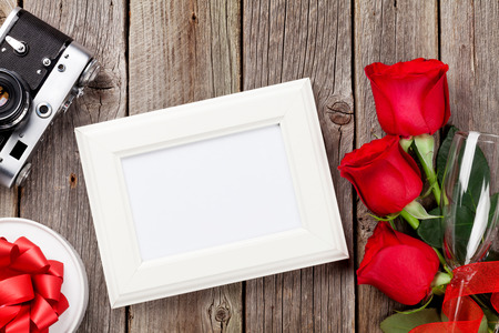 frame  box: Valentines day roses, photo frame, retro camera and gift box over wooden background
