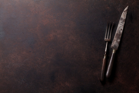 grunge cutlery: Old vintage kitchen utensils on stone table. Top view with copy space Stock Photo