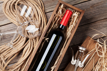 Red wine bottle in box and glasses on wooden table. Top view