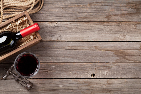 Red wine bottle and glass on wooden table. Top view with copyspace