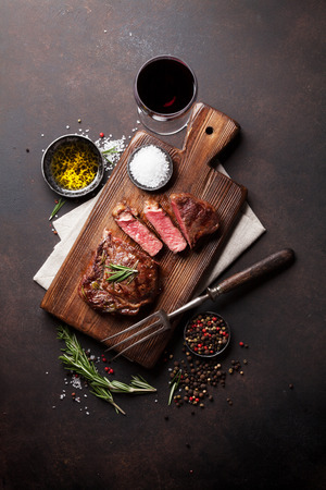 Grilled ribeye beef steak with red wine, herbs and spices. Top view