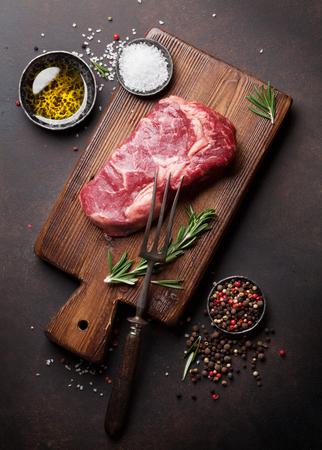 Raw ribeye beef steak cooking with ingredients. Top view