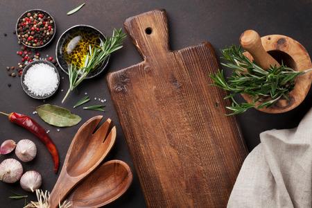 Koken tafel met kruiden, specerijen en keukengerei. Bovenaanzicht met een kopie ruimte
