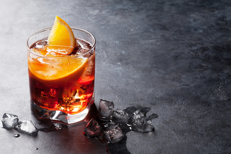 Negroni cocktail on dark stone table. With space for your text Standard-Bild
