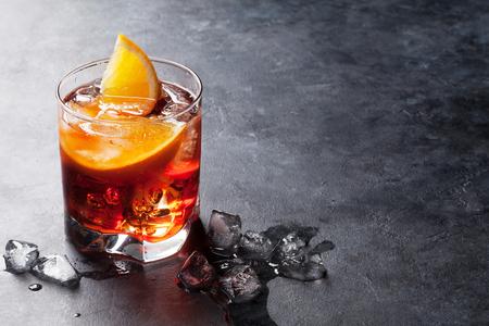 Negroni-cocktail op donkere stenen tafel. Met ruimte voor uw tekst