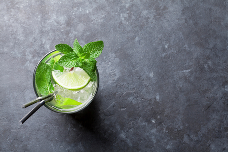 Mojito cocktail op donkere stenen tafel. Bovenaanzicht met ruimte voor uw tekst