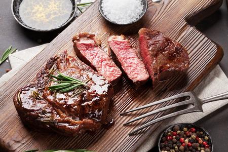 carne asada: Filete de ternera a la parrilla, hierbas y especias en la tabla de cortar Foto de archivo