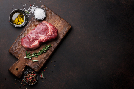 Raw ribeye beef steak cooking with ingredients. Top view with copy space Banque d'images