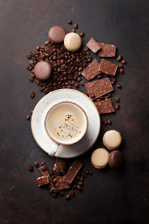 Coffee cup, beans, chocolate and macaroons on old kitchen table. Top view