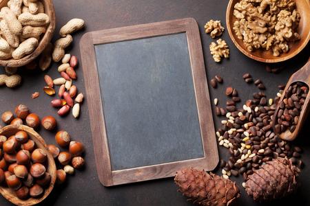 Verschillende noten op stenen tafel. Bovenaanzicht met bord voor kopieerruimte Stockfoto