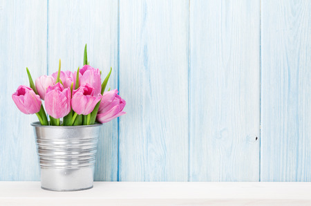 Fresh pink tulip flowers bouquet on shelf in front of wooden wall. View with copy space