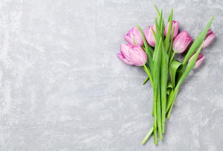 Verse paarse tulp bloemen op stenen tafel. Bovenaanzicht met een kopie ruimte