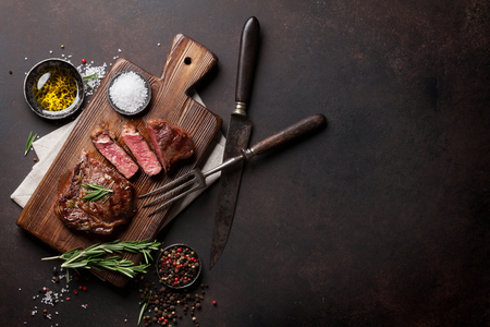 Grilled ribeye beef steak, herbs and spices. Top view with copy space for text