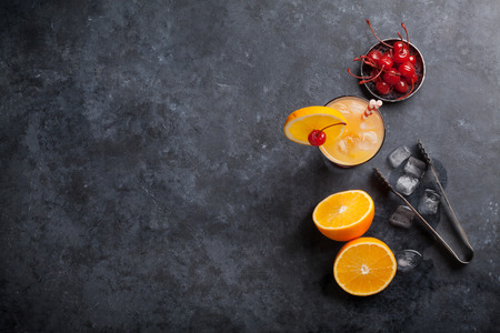 Tequila sunrise cocktail on dark stone table. Top view with space for text