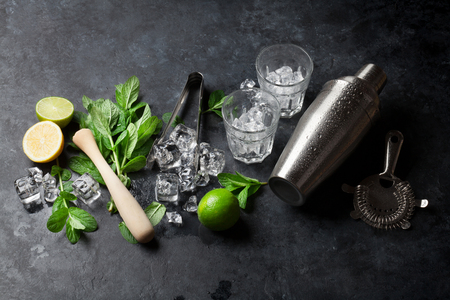 lime: Mojito cocktail making. Mint, lime, ice ingredients and bar utensils