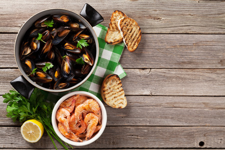 Mussels and shrimps on wooden table. Top view with copy space Stock Photo