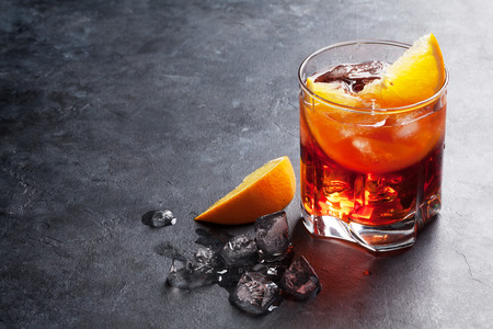 Negroni cocktail op donkere stenen tafel. Met ruimte voor tekst