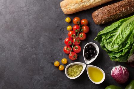 요리 음식 재료. 양상추 샐러드, 아보카도, 올리브, 빵 및 토마토 체리 돌 배경 위에. 복사 공간이있는 상위 뷰