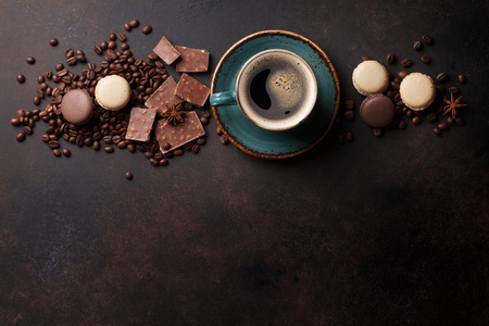 Coffee cup, beans, chocolate and macaroons on old kitchen table. Top view with copyspace for text
