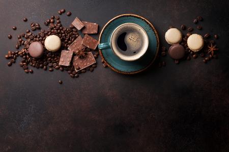 Koffiekopje, bonen, chocolade en macaroons op oude keukentafel. Bovenaanzicht met copyspace voor tekst
