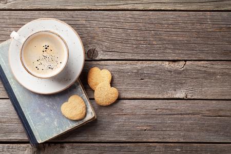 커피 컵과 심장 모양의 쿠키 나무 테이블에. 발렌타인 데이. 인사말을위한 공간이있는 윗면보기