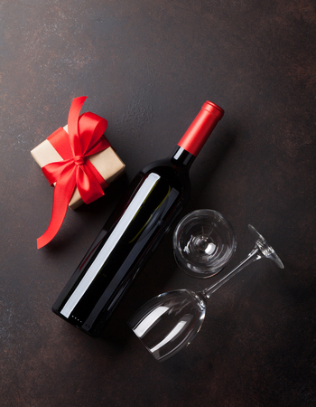 wine gift: Valentines day greeting card. Red wine, gift box and glasses on stone table. Top view