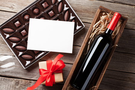 Valentines day greeting card. Red wine, gift box and chocolate box on wooden table. Top view with space for greetings