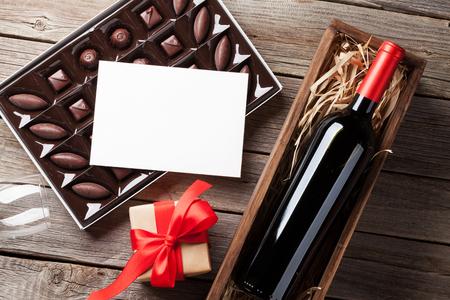 San Valentín tarjeta de felicitación del día. El vino tinto, caja de regalo y caja de chocolate en la mesa de madera. Vista superior con espacio para los saludos