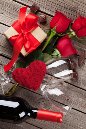 wine gift: Valentines day greeting card. Red rose flowers, wine, gift box and sweets on wooden table. Top view Stock Photo