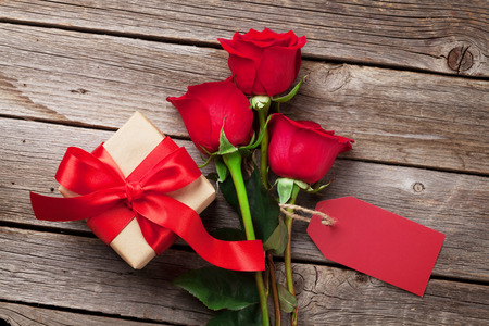 red gift box: Valentines day greeting card, red rose flowers and gift box on wooden table. Top view with copy space Stock Photo