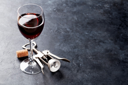 Red wine glass and corkscrew on stone background. With copy space Фото со стока