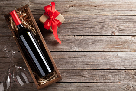 wine gift: Valentines day greeting card. Red wine, gift box and glasses on wooden table. Top view with space for your greetings