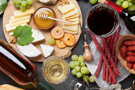 Red and white wine, grape, cheese and sausages on stone table. Top view