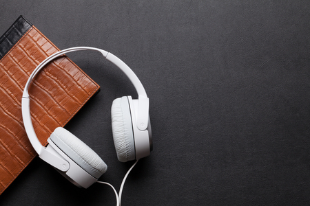 chillout: Headphones and notepad on black leather desk table. Music concept. Top view with copy space