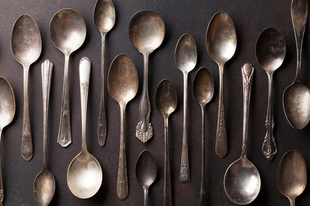 grunge silverware: Old vintage spoons on stone table. Top view