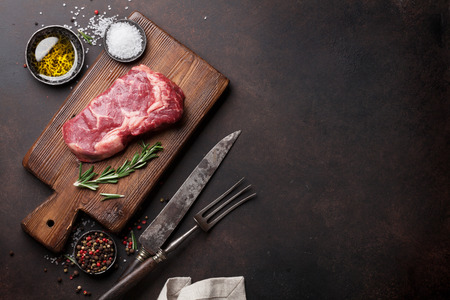Raw ribeye beef steak cooking with ingredients. Top view with copy space Stock Photo
