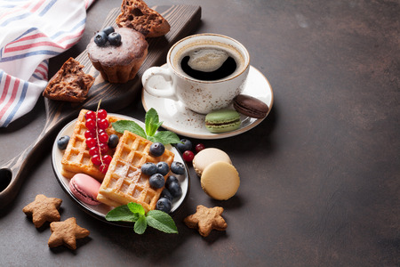 Coffee, sweets and waffles with berries. View with copy space