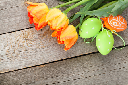 huevo: Huevos de Pascua y flores de tulipán en la mesa de madera. Vista superior con espacio de copia Foto de archivo