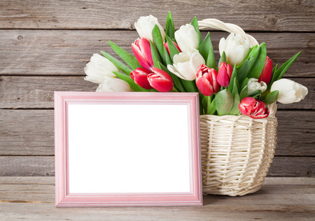 Colorful tulips bouquet basket and blank photo frame in front of wooden wall. Red and white. With copy space