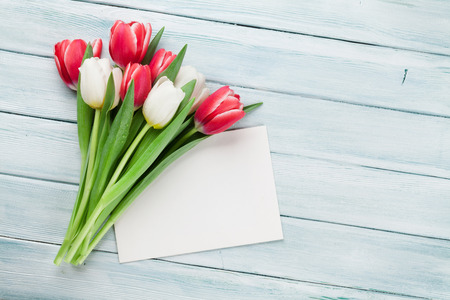 Colorful tulips bouquet on wooden background. Red and white. Top view with greeting card for text