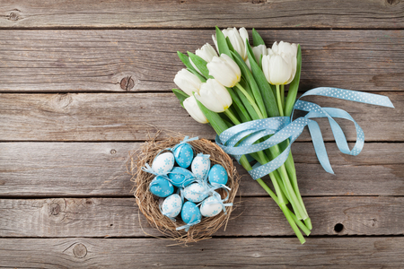 Easter eggs in nest and white tulips on wooden background. Top view with space for greetings