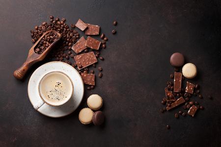 Taza de café, frijoles, chocolate y macarrones en la vieja mesa de la cocina. Vista superior con copyspace para texto