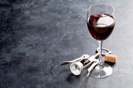 Red wine glass and corkscrew on stone table. With copy space