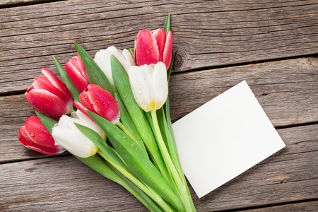 Colorful tulips bouquet and blank greeting card on wooden background. Red and white. Stock Photo