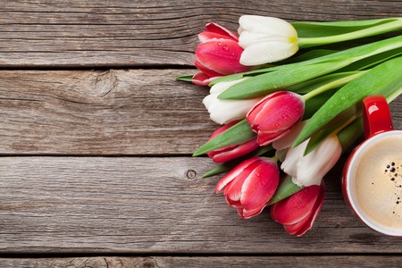 Colorful tulips bouquet and coffee cup on wooden background. Red and white. With space for greetings